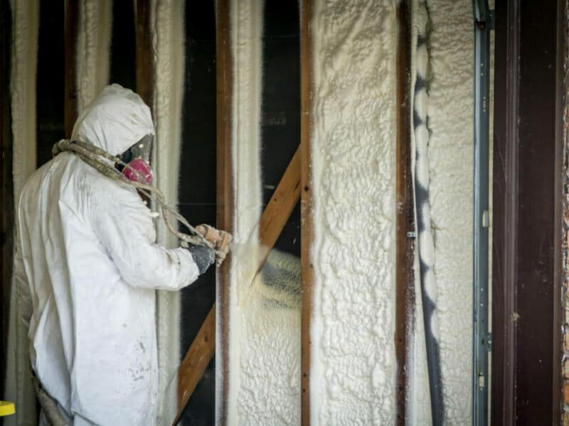 un technicien projette de la mousse polyuréthane sur un mur pour l'isoler